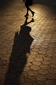 Silhouette of young woman walking alone in amber sunset shadows