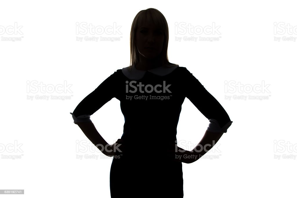 Silhouette of young woman with hands on hip stock photo