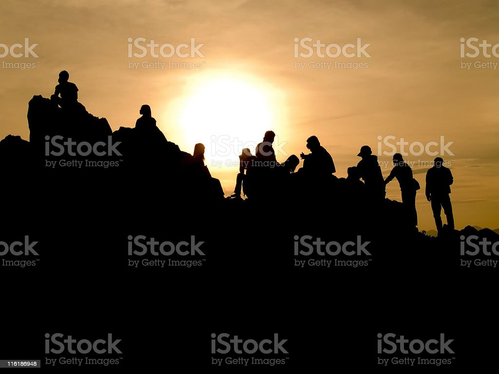 Silhouette people on top of the mountain at sunset stock photo