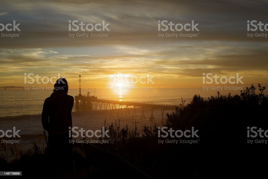 Silhouette Person looking out to Pier Sunset royalty-free stock photo