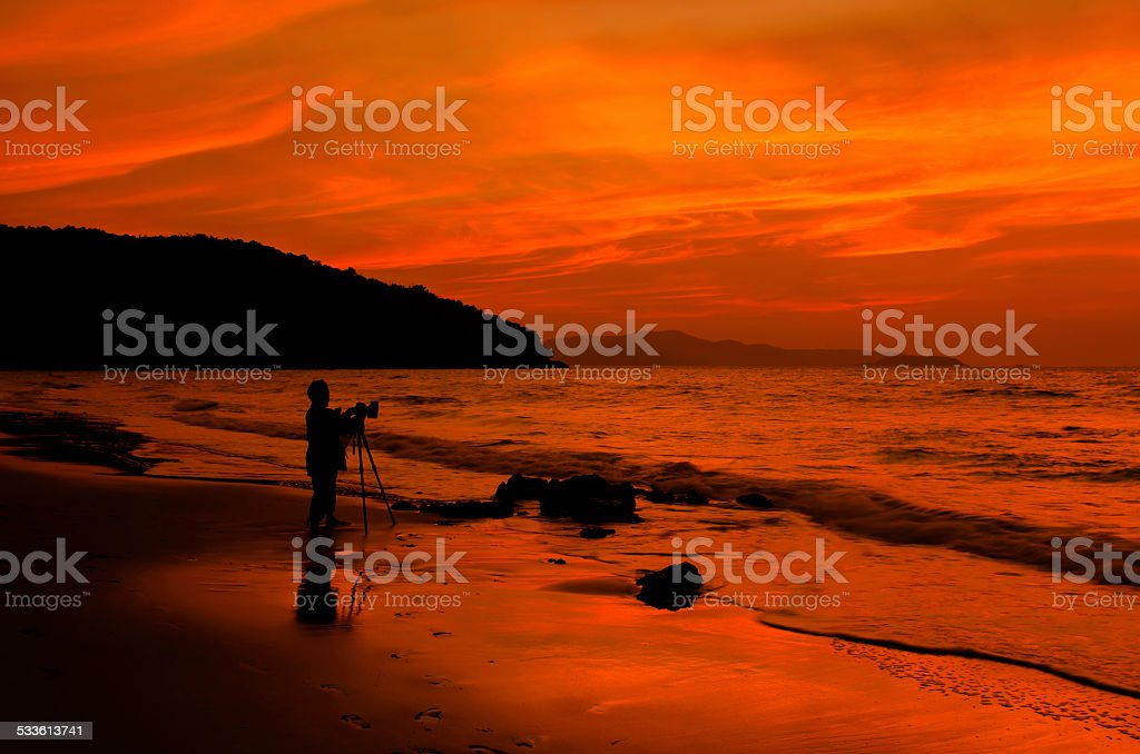 Silhouette photographer's man at the beach stock photo