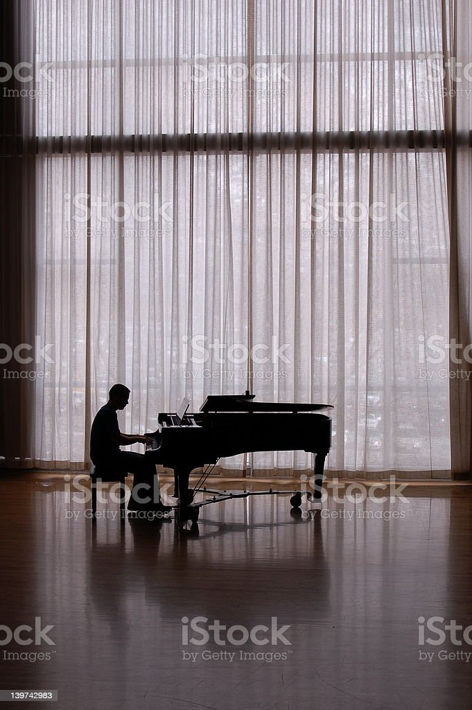 silhouette piano in a sunlit studio stock photo