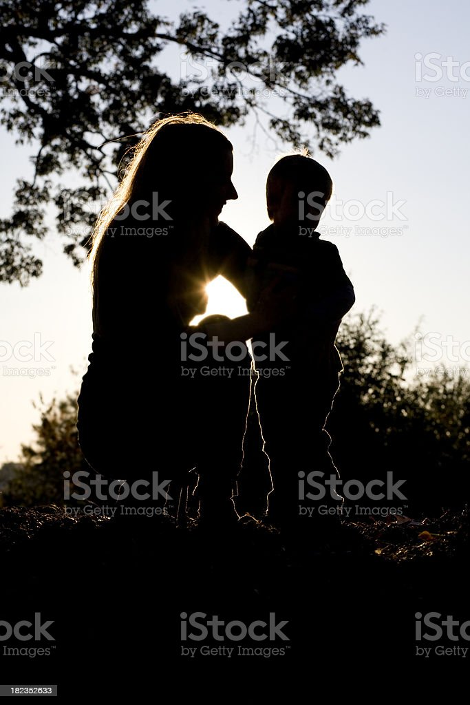 A silhouette picture of a mother and her child in the park royalty-free stock photo