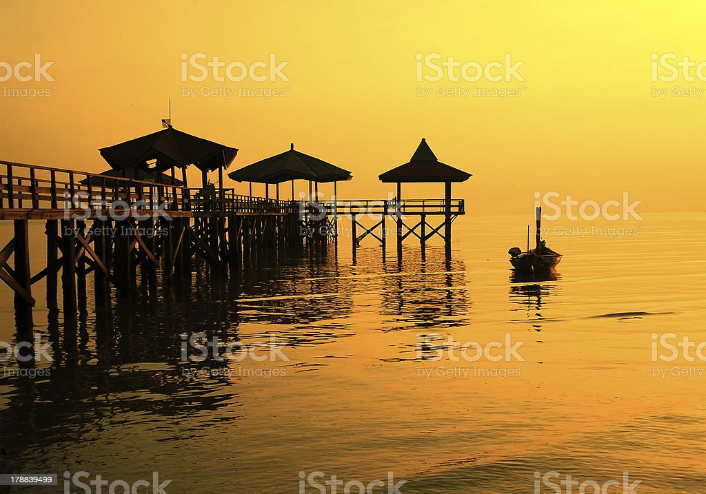 Silhouette pier beside boat on the shore stock photo