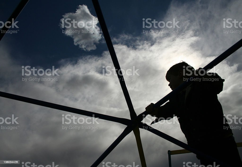 A silhouette portrait of a boy playing at the playground royalty-free stock photo