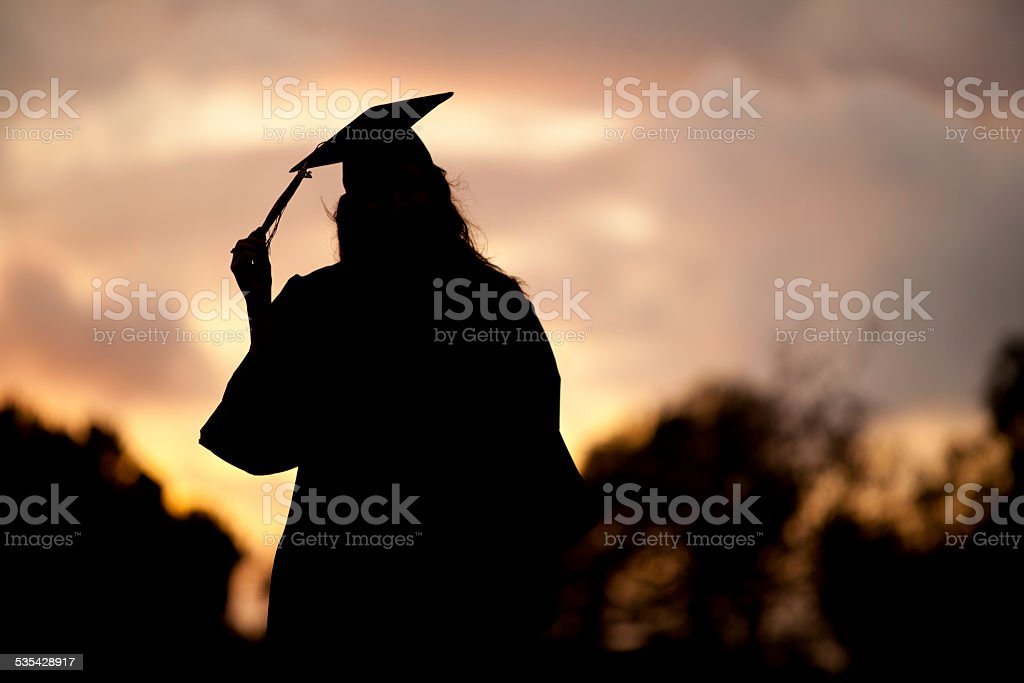 Silhouette Portrait of a graduate in cap and gown stock photo