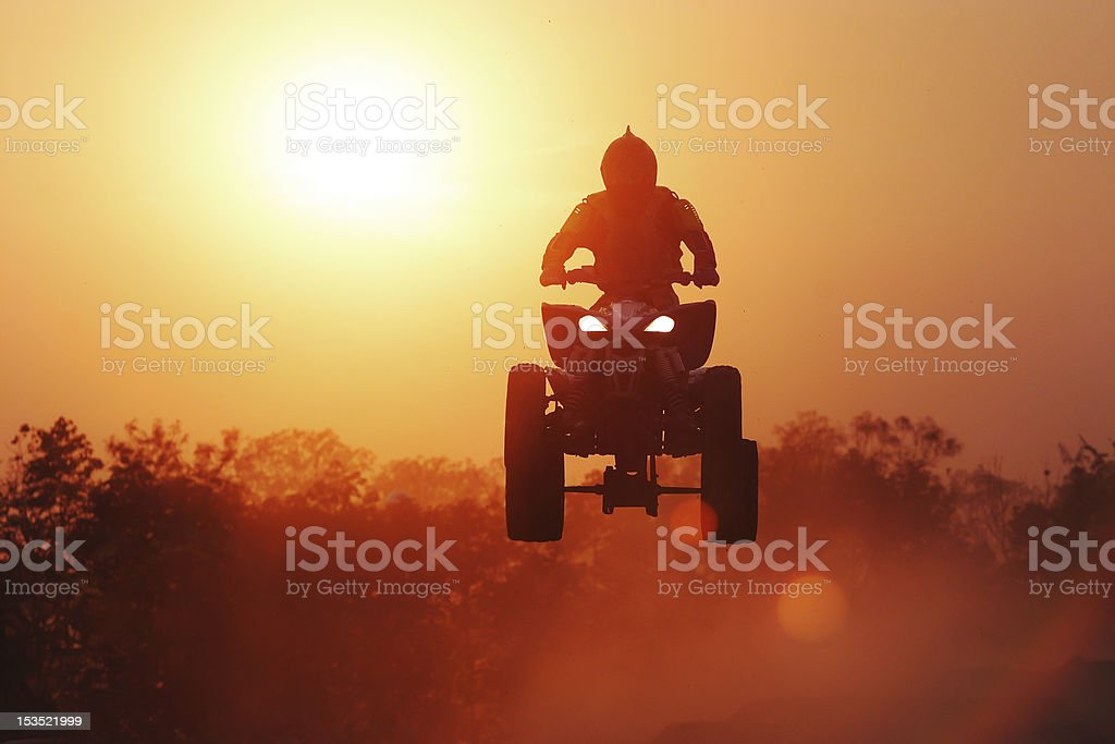 Silhouette Quadbike jumping in track. stock photo