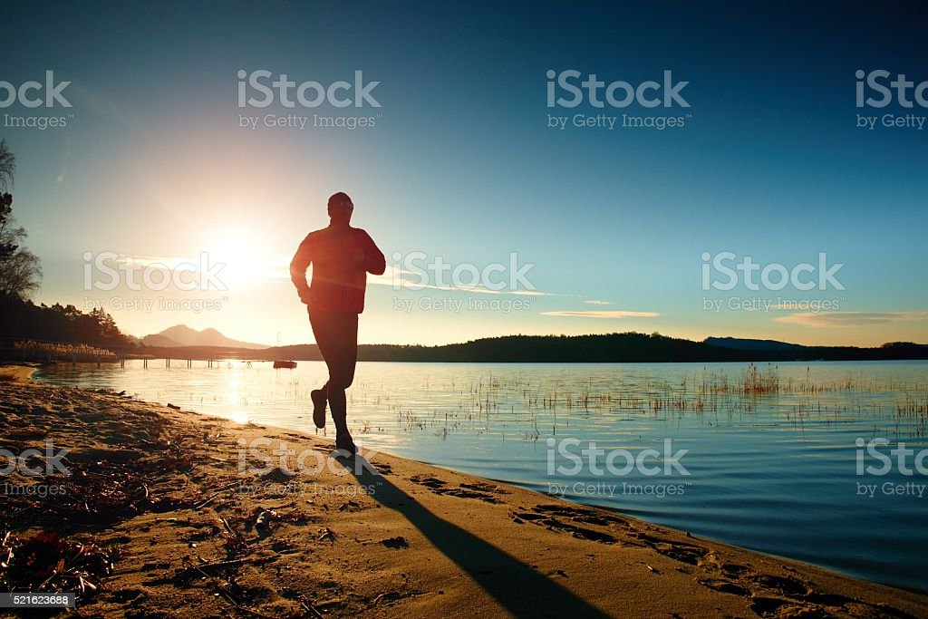 Silhouette running and exercising on the beach at sunset. stock photo