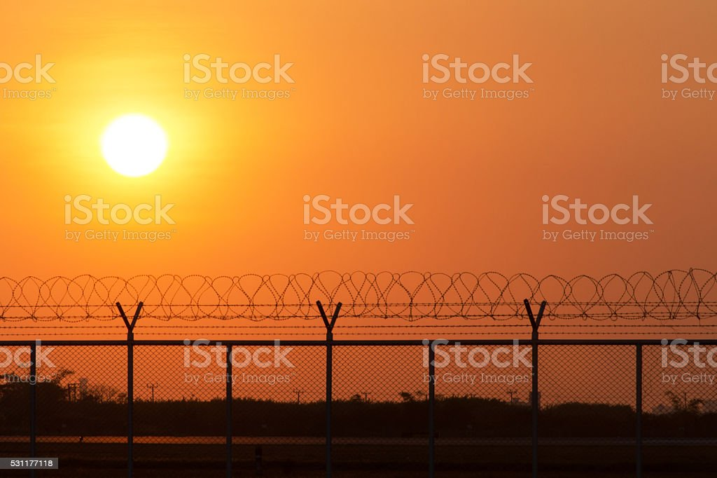 Silhouette security with a barbed wire fence at sunset time stock photo