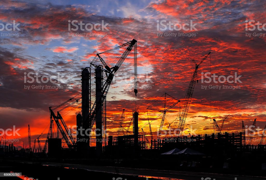 Silhouette shot of multiple cranes in construction sites. stock photo