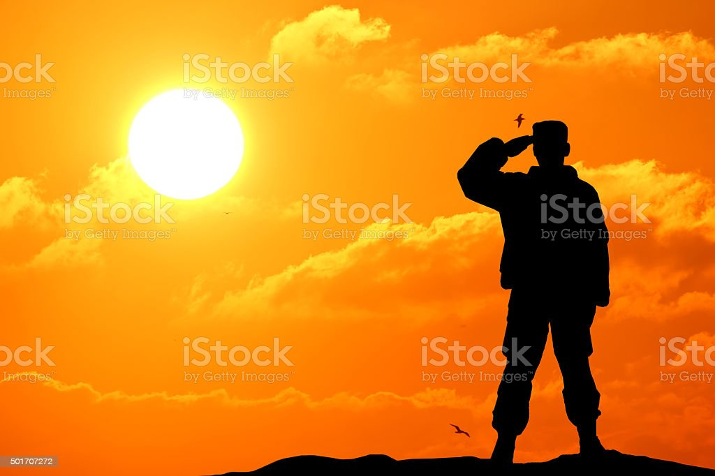 Silhouette shot of soldier holding gun with colorful sky stock photo