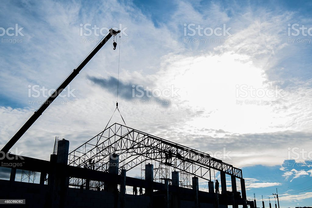 Silhouette steel frame construction and crane at site construction stock photo