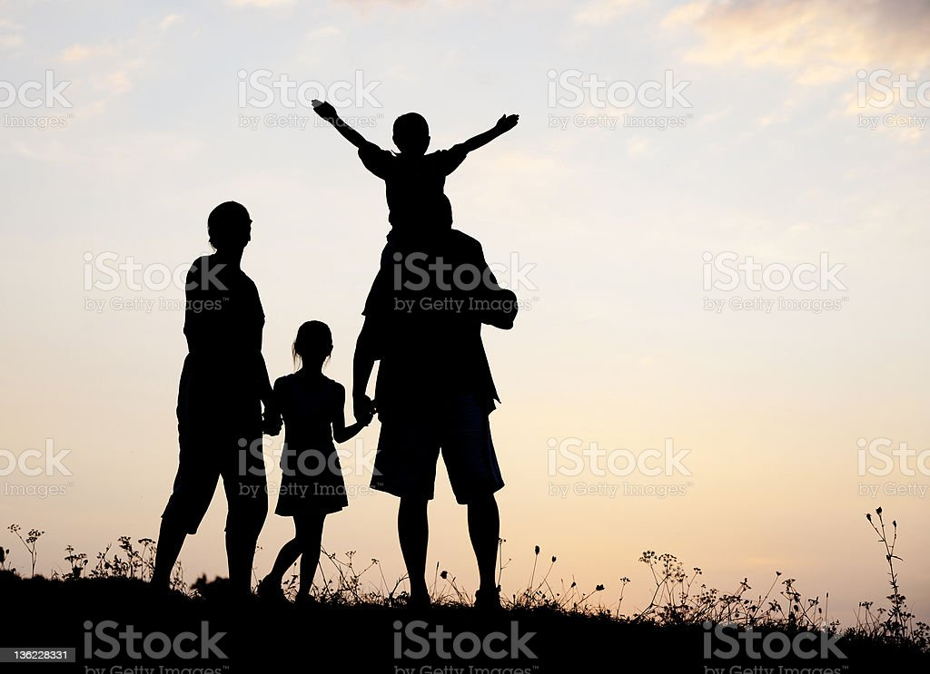 Silhouette style photo of happy family playing in meadow royalty-free stock photo