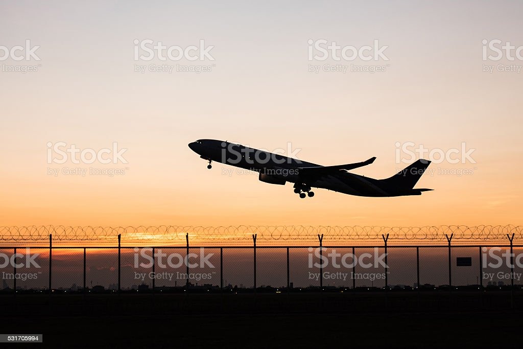 Silhouette takeoff plane while sunset stock photo
