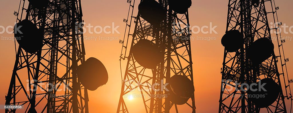 Silhouette, telecommunication towers with TV antennas and satellite dish stock photo