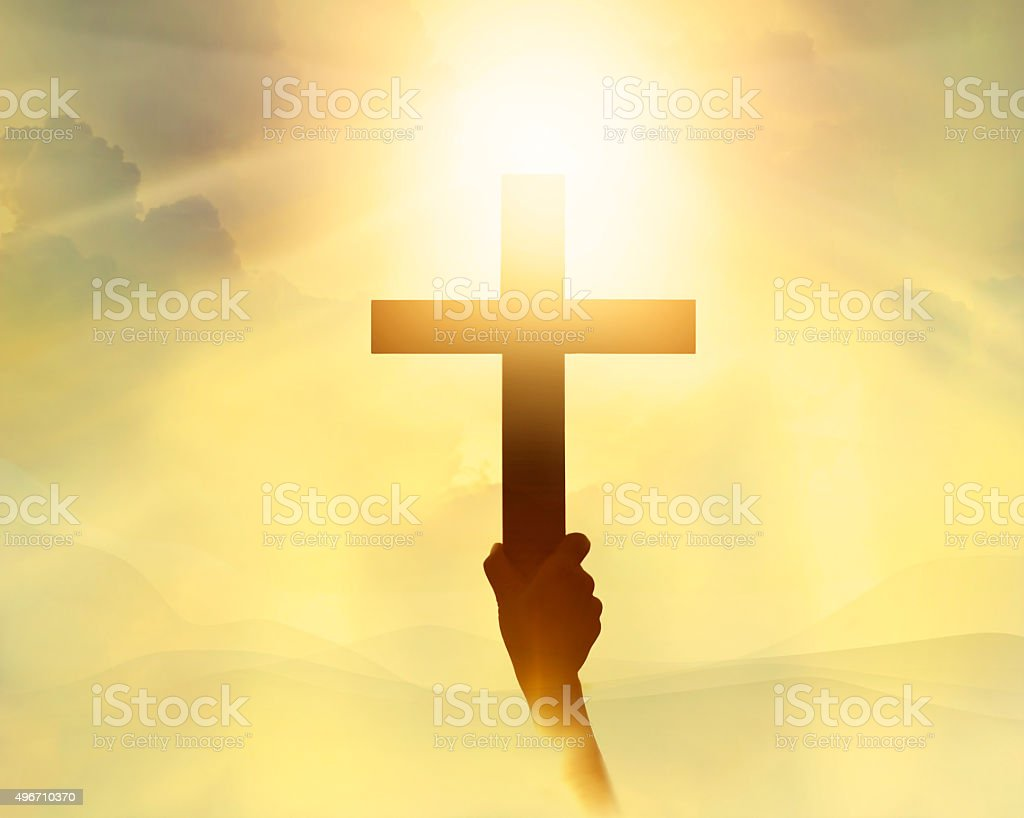 Silhouette the cross in hand, religion symbol in light stock photo