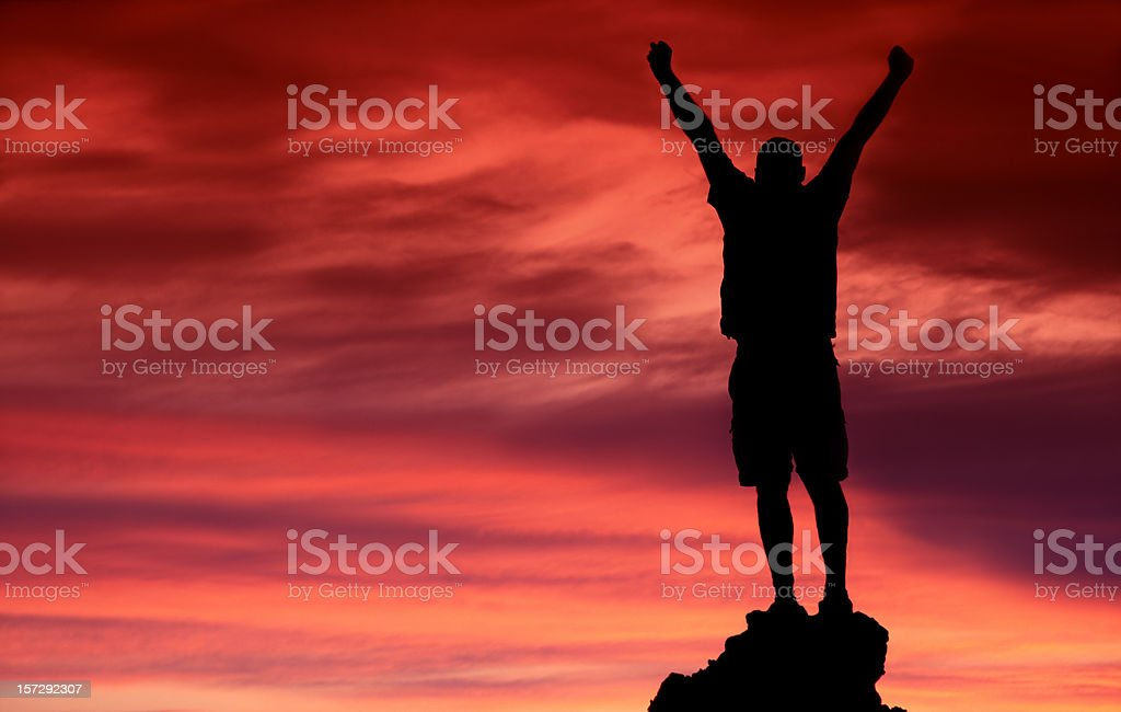 Silhouette Unrecognizable Male Raising His Arms in Victory stock photo