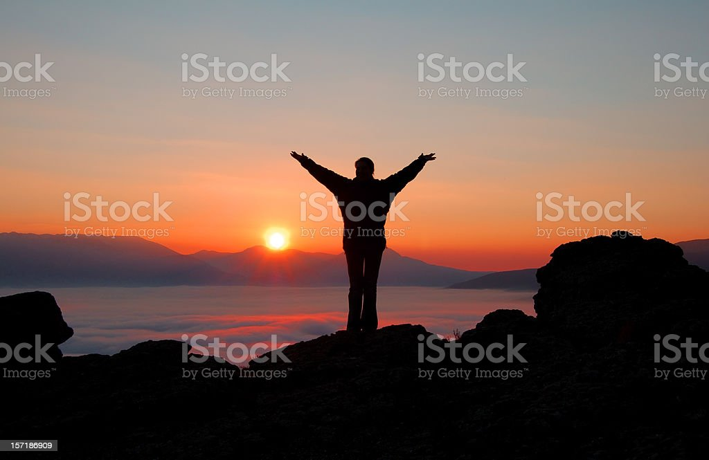silhouette up hands in mountains on crimson sunset stock photo