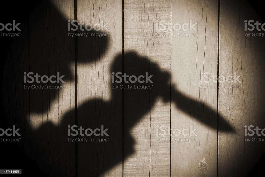 Silhouette with knife on the Natural Wooden Panel stock photo