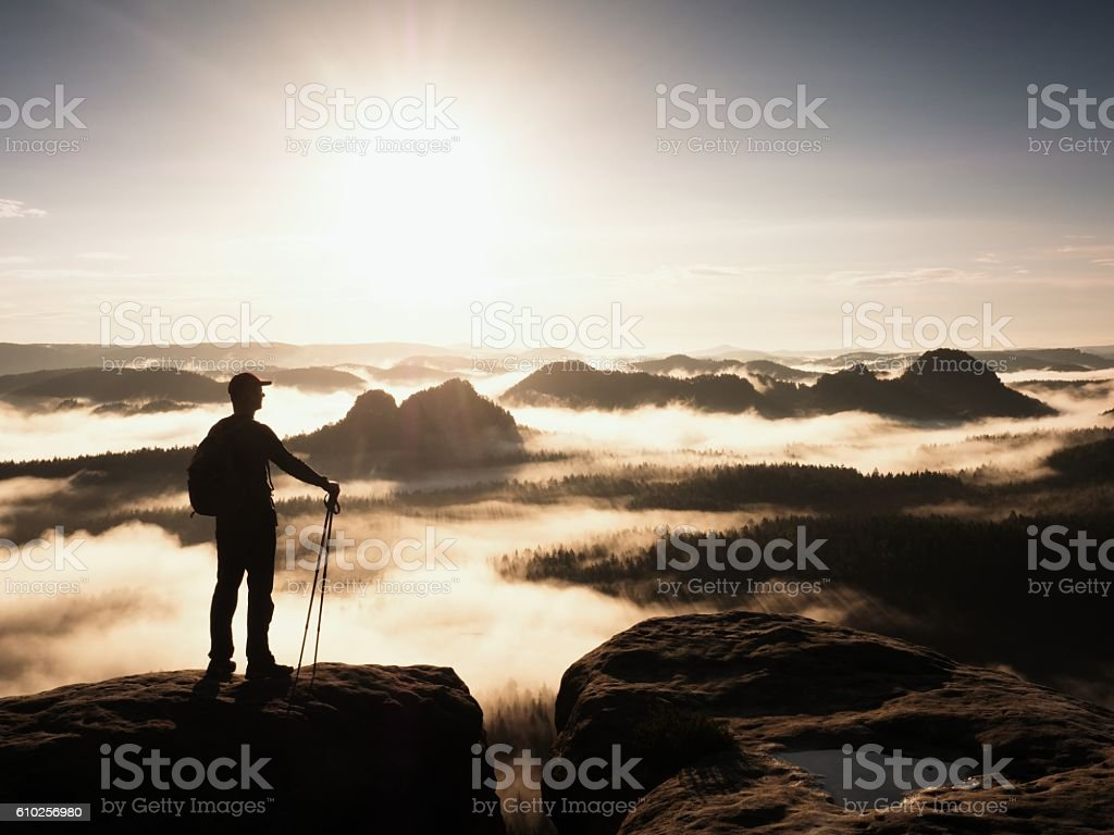 Silhouette with poles in hand. Sunny spring daybreak in mountains. stock photo