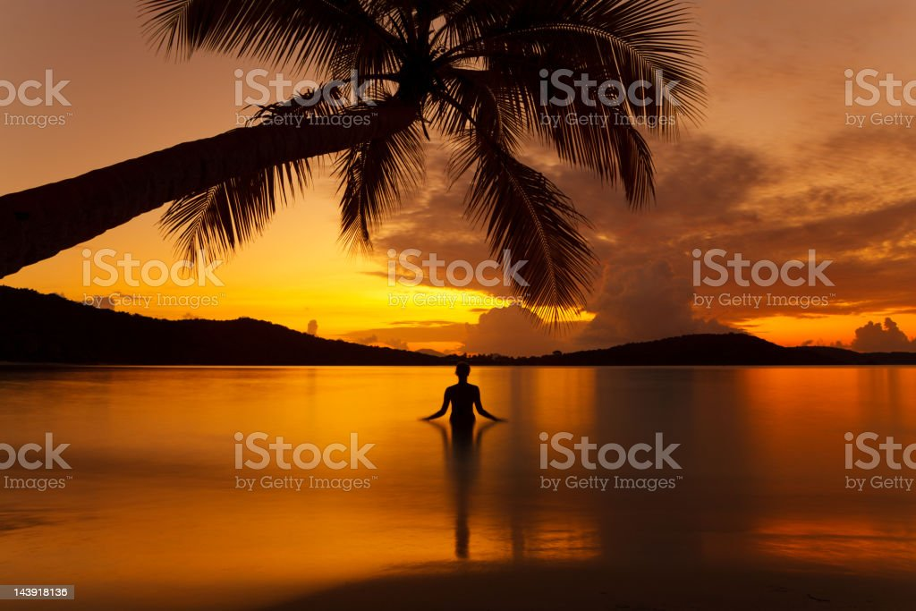 silhouette woman meditating in water during sunset at a beach royalty-free stock photo