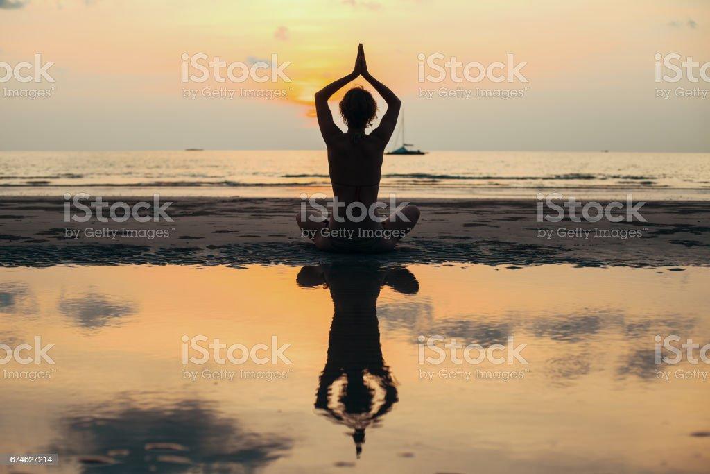 Silhouette yoga woman meditating at the sea shore. stock photo