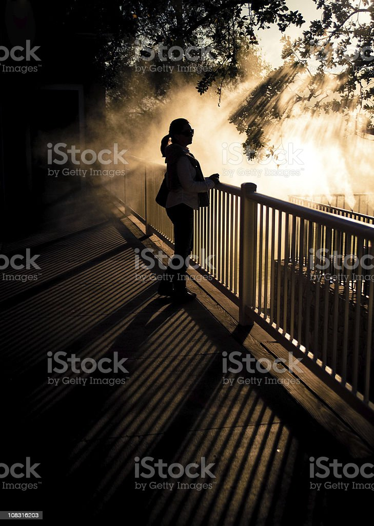 silhouette young woman standing in a balcony stock photo