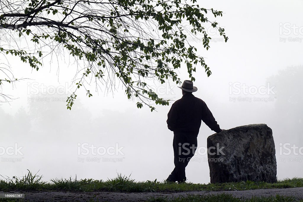 Silhouetted Adult Male Stands Alone Thoughtfully Staring Towards Foggy Lake royalty-free stock photo
