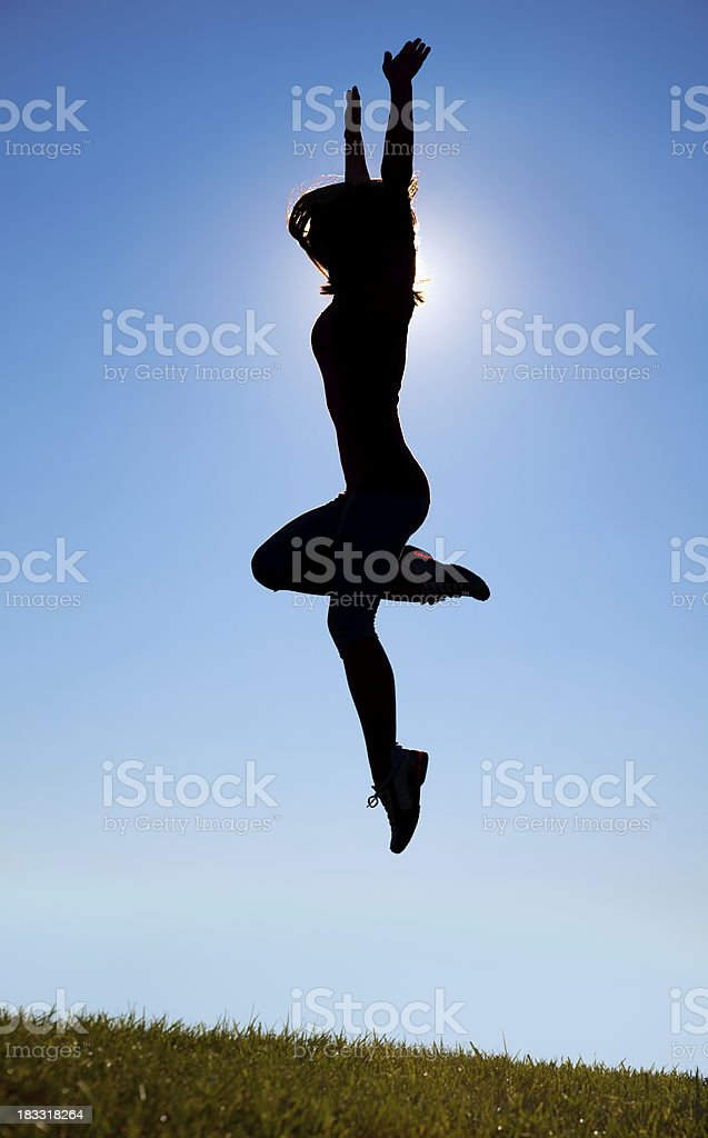 Silhouetted Athlete Girl Jumping Joyously High in Air royalty-free stock photo
