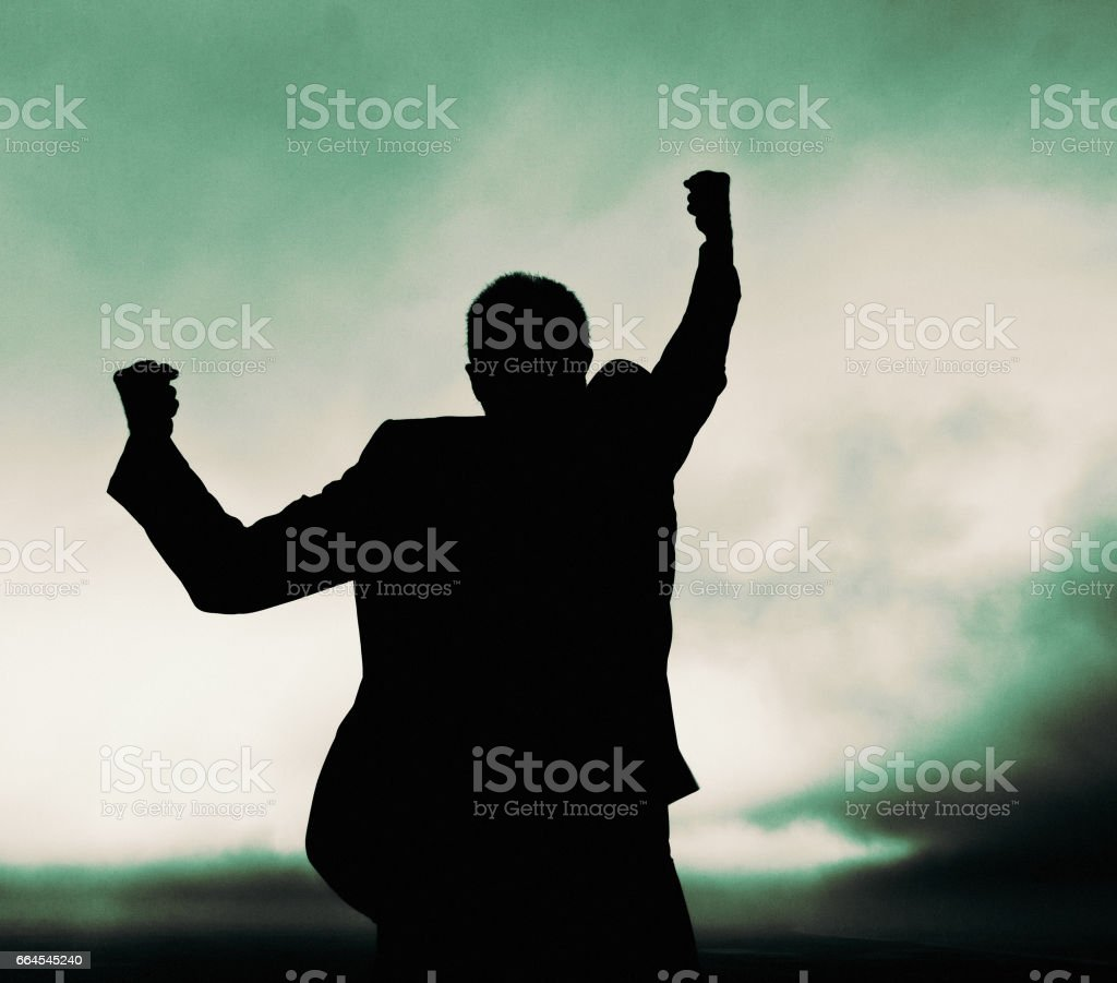 Silhouetted businessman shaking fist at stormy sky in frustrated anger stock photo