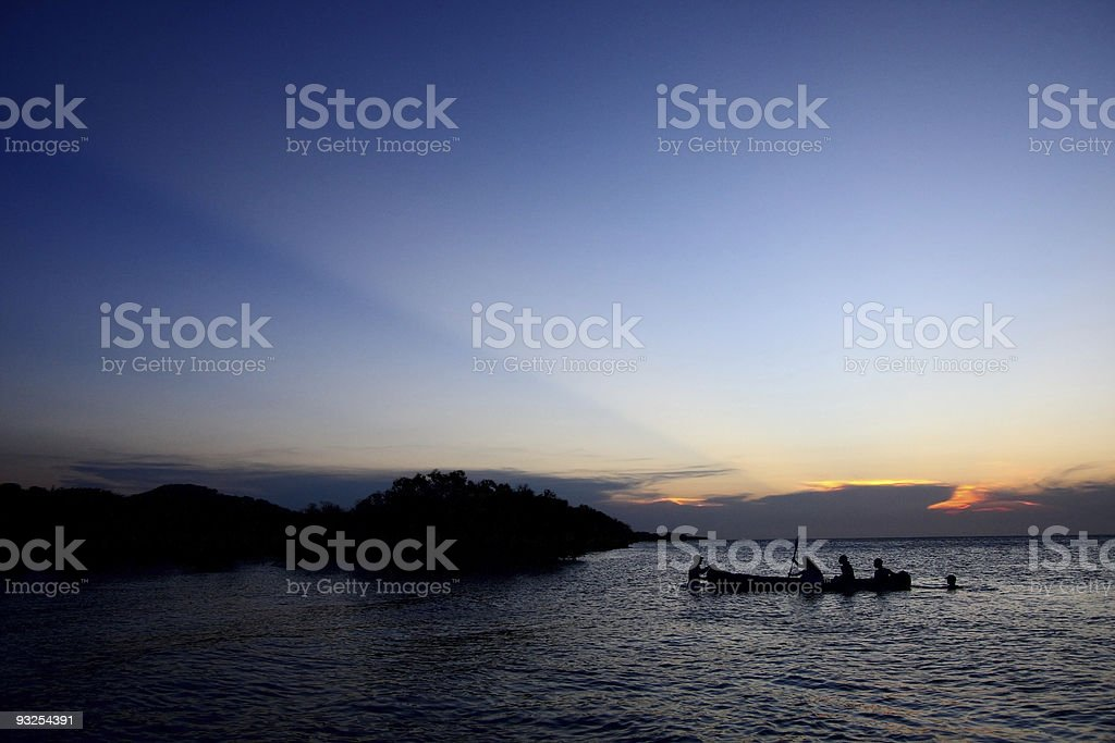Silhouetted Canoe in Mozambique stock photo