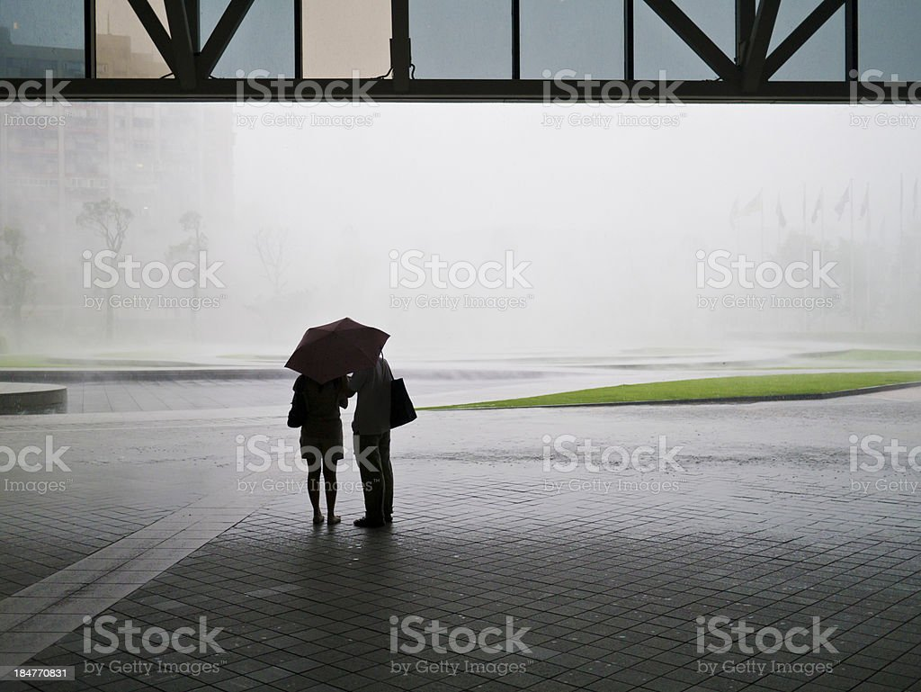silhouetted couple with heavy rain royalty-free stock photo