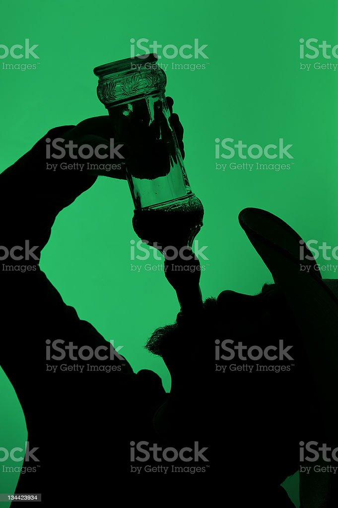 Silhouetted Cowboy Drinking Alcohol from Bottle stock photo