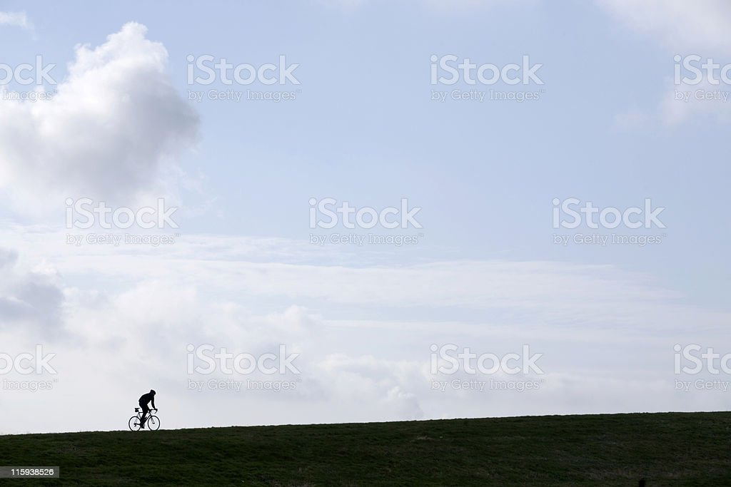 silhouetted cyclist climbing a hill royalty-free stock photo