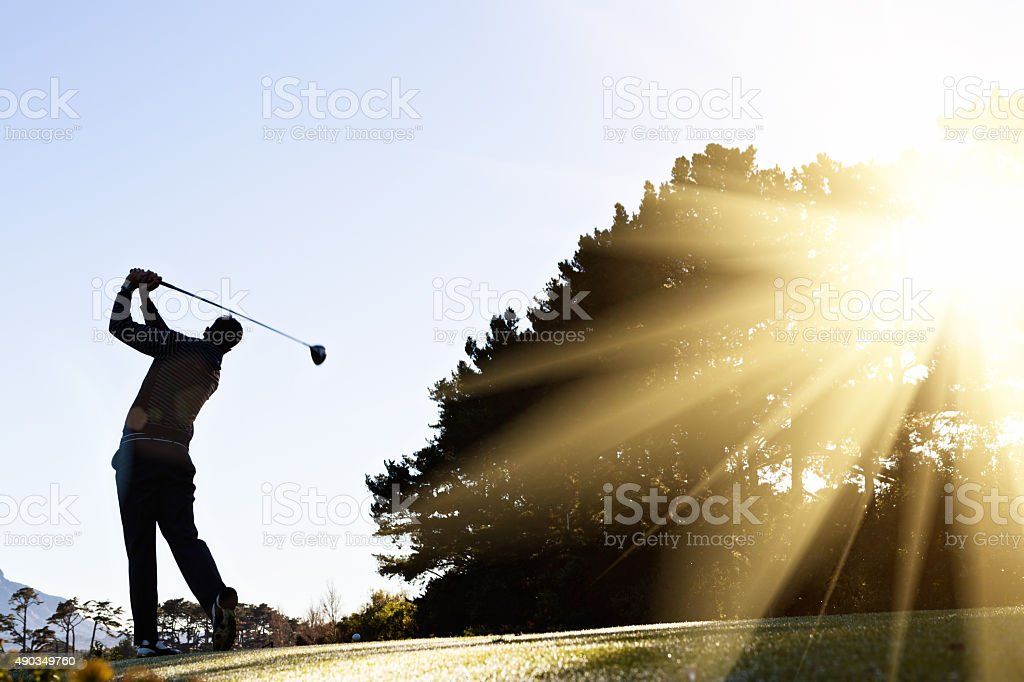 Silhouetted early morning golfer makes his swing stock photo