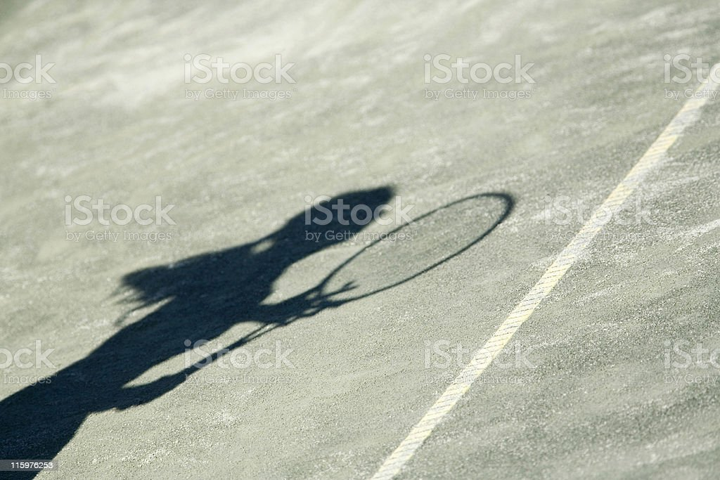 silhouetted female tennis player on a playing court royalty-free stock photo