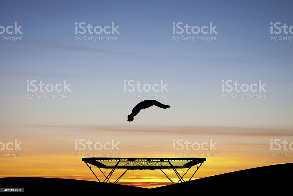 silhouetted gymnast on trampoline at sunset stock photo
