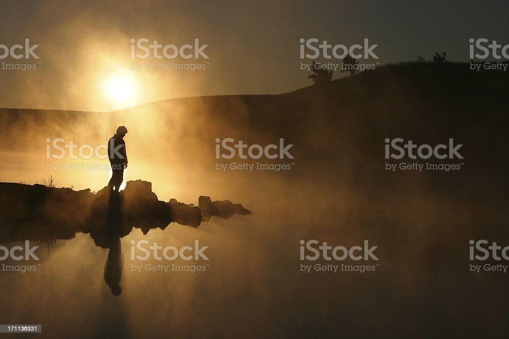 Silhouetted Hiker Warm Sunrise over Foggy Lake royalty-free stock photo