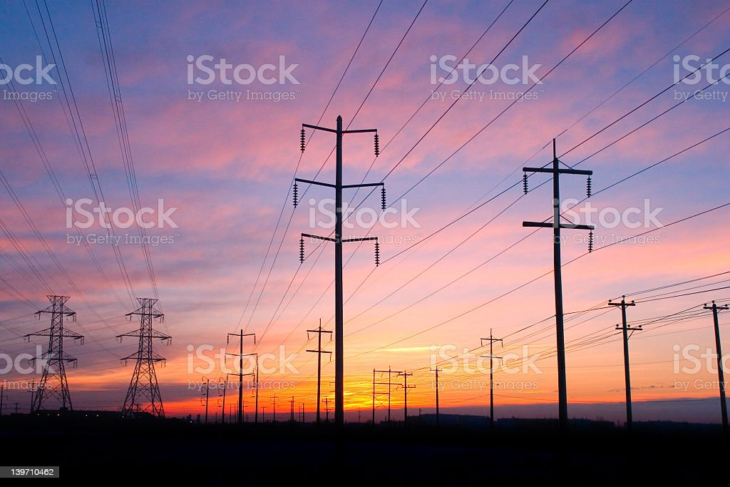Silhouetted image of power lines at sunset royalty-free stock photo
