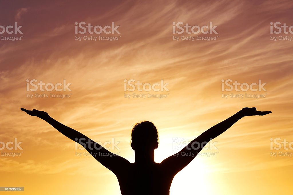 Silhouetted lady with arms out against beautiful sky at sunset royalty-free stock photo