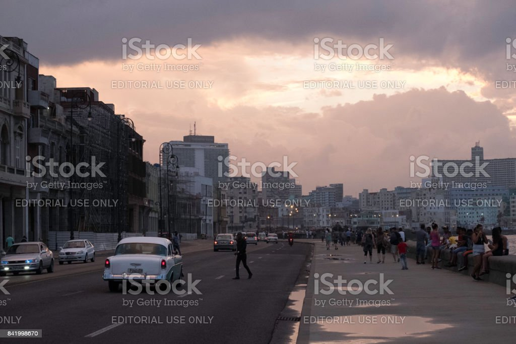 Silhouetted man crossing waterfront parkway road at sunset stock photo