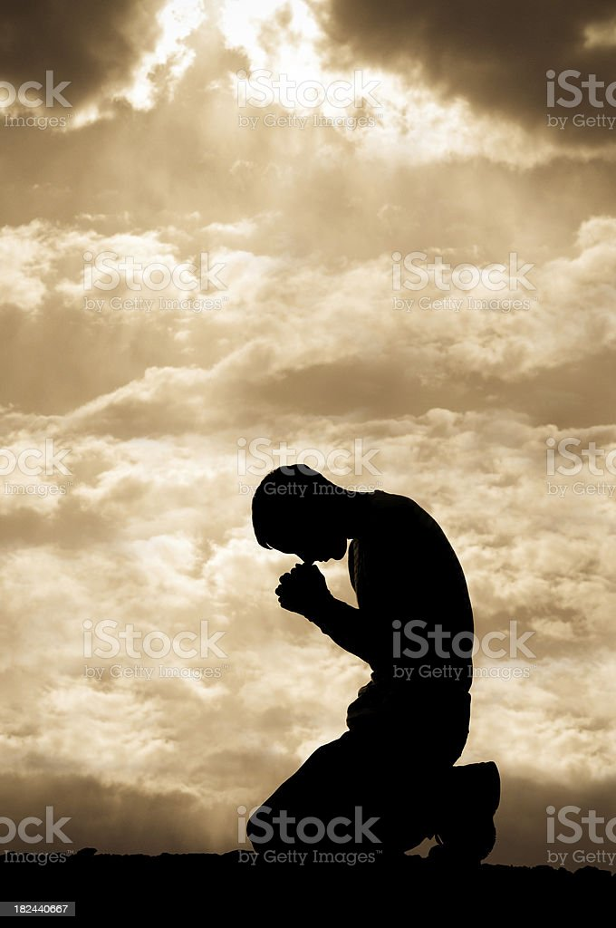 Silhouetted man on his knees praying stock photo
