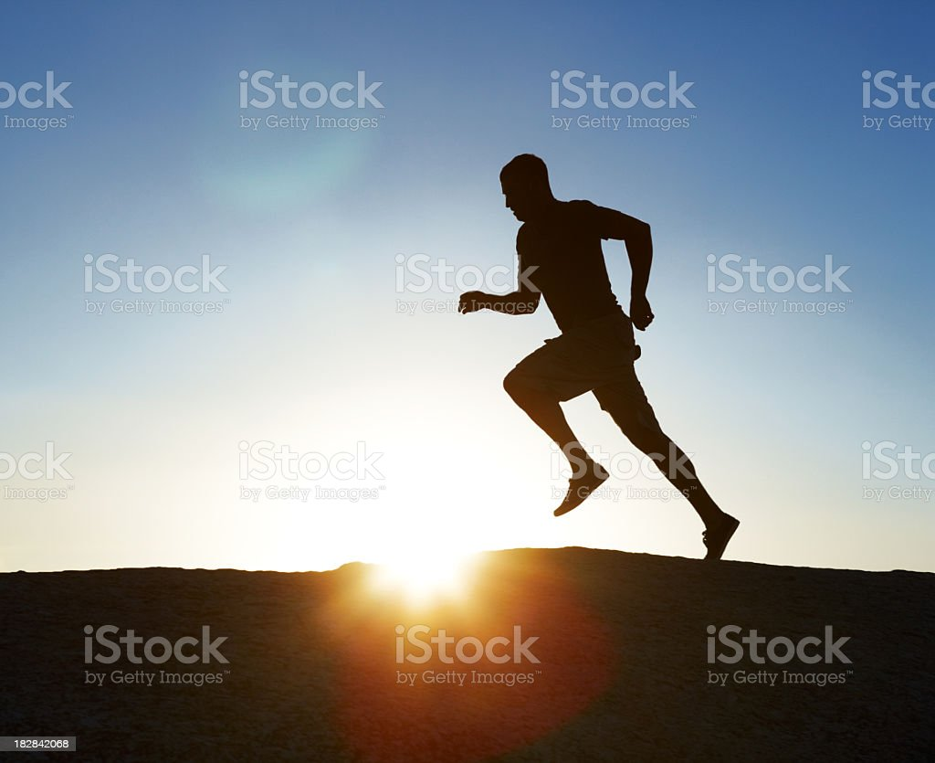 Silhouetted man running at sunset royalty-free stock photo