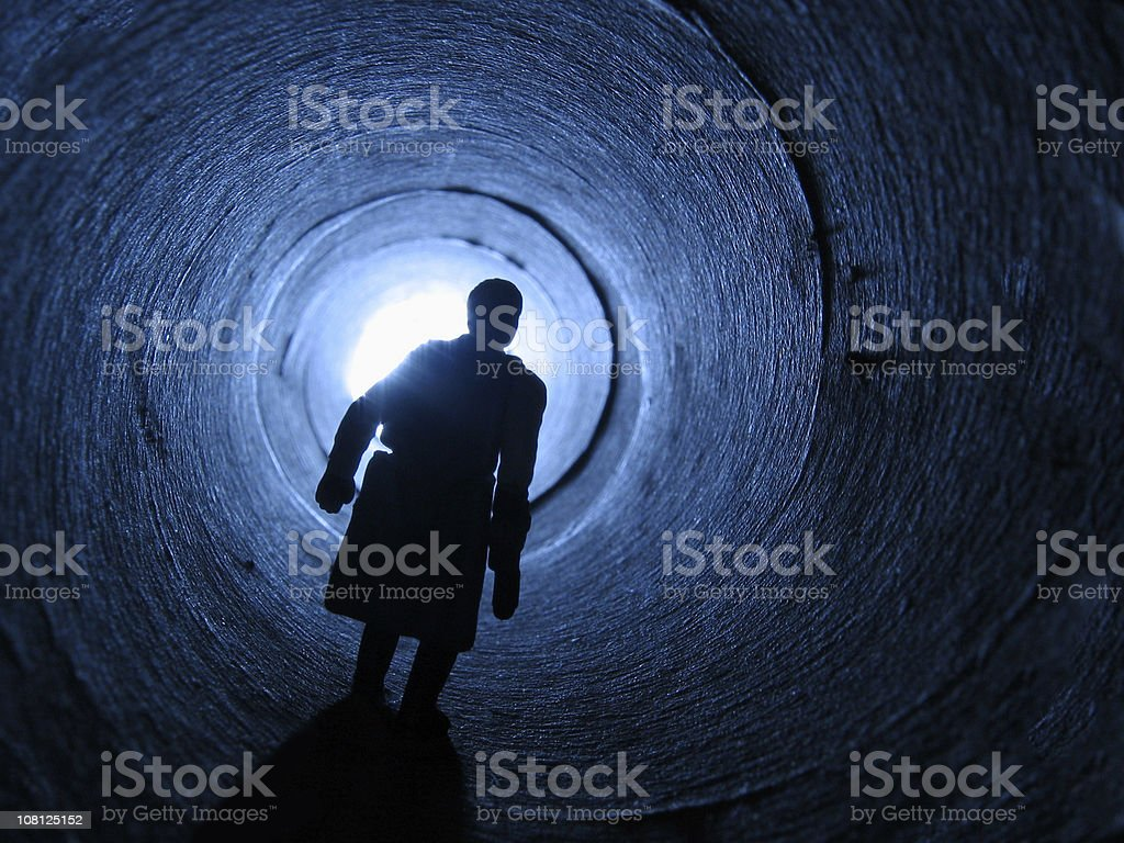 Silhouetted man walking towards light at end of tunnel royalty-free stock photo