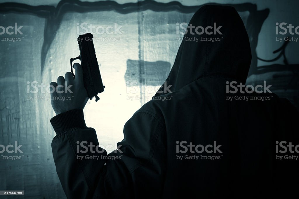Silhouetted man with gun stock photo