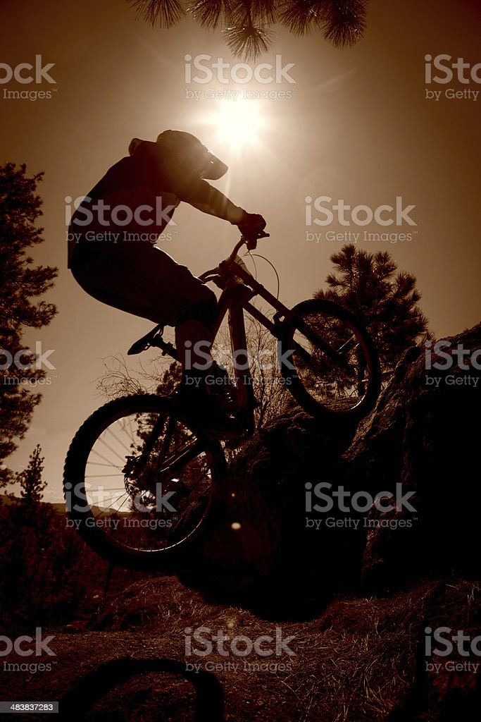 Silhouetted mountain biker catching air off of a jump. royalty-free stock photo