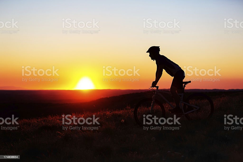 Silhouetted mountain biker royalty-free stock photo