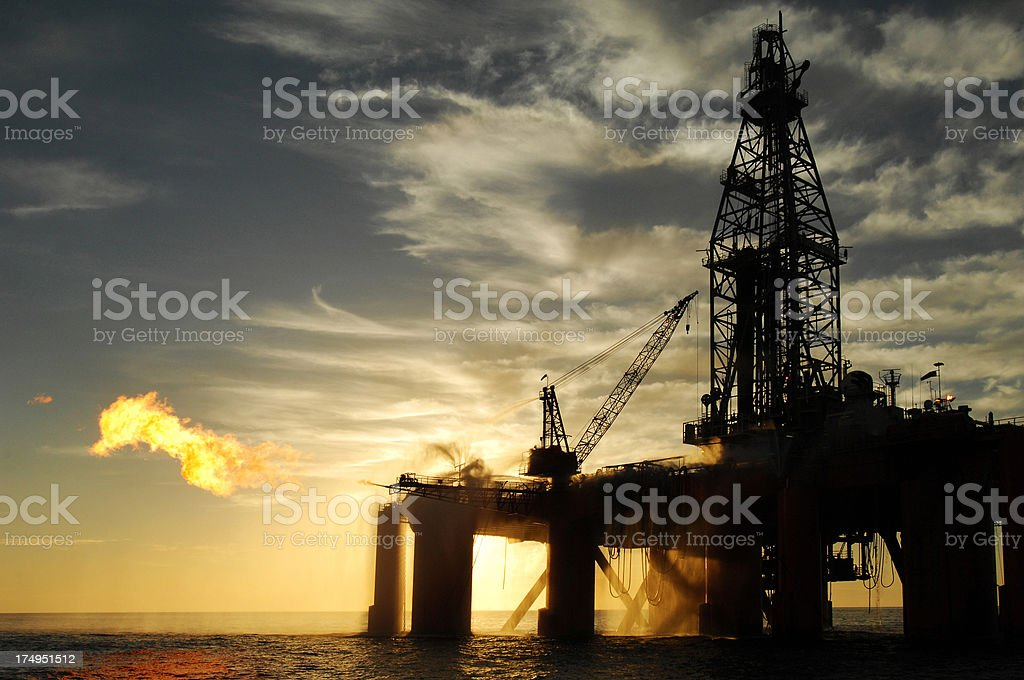 Silhouetted oil rig with a large gas flare. stock photo