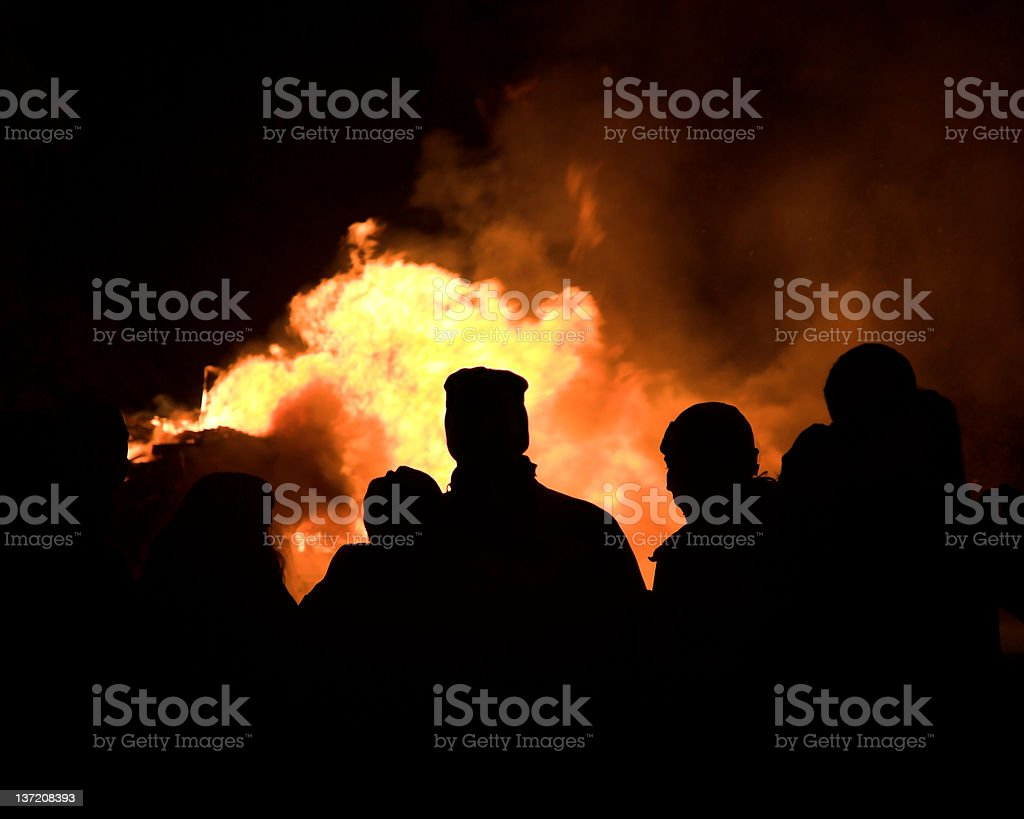 Silhouetted people around a bonfire at night royalty-free stock photo