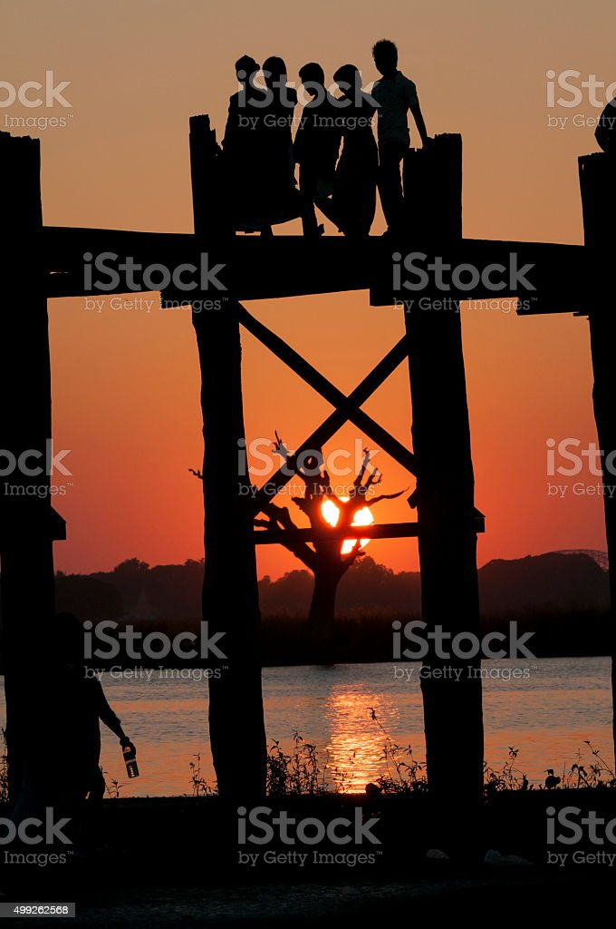Silhouetted people at sunset on U Bein Bridge in Myanmar stock photo